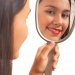 Beautiful Girl Looking At A Hand Mirror And Smiling